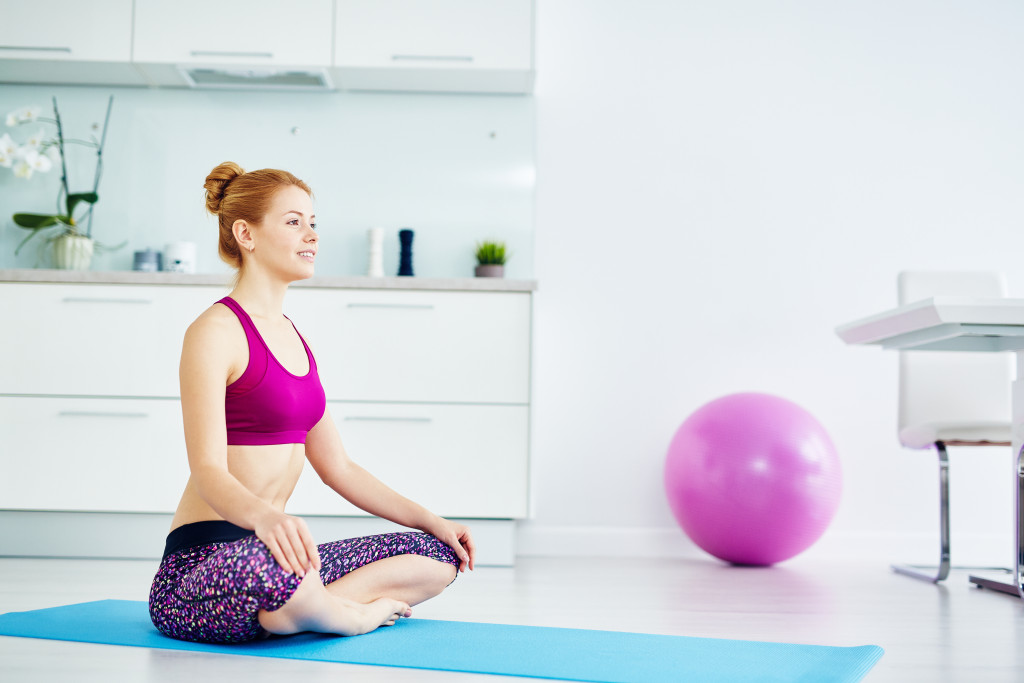 Portrait of fit red haired woman doing yoga exercises at home on floor