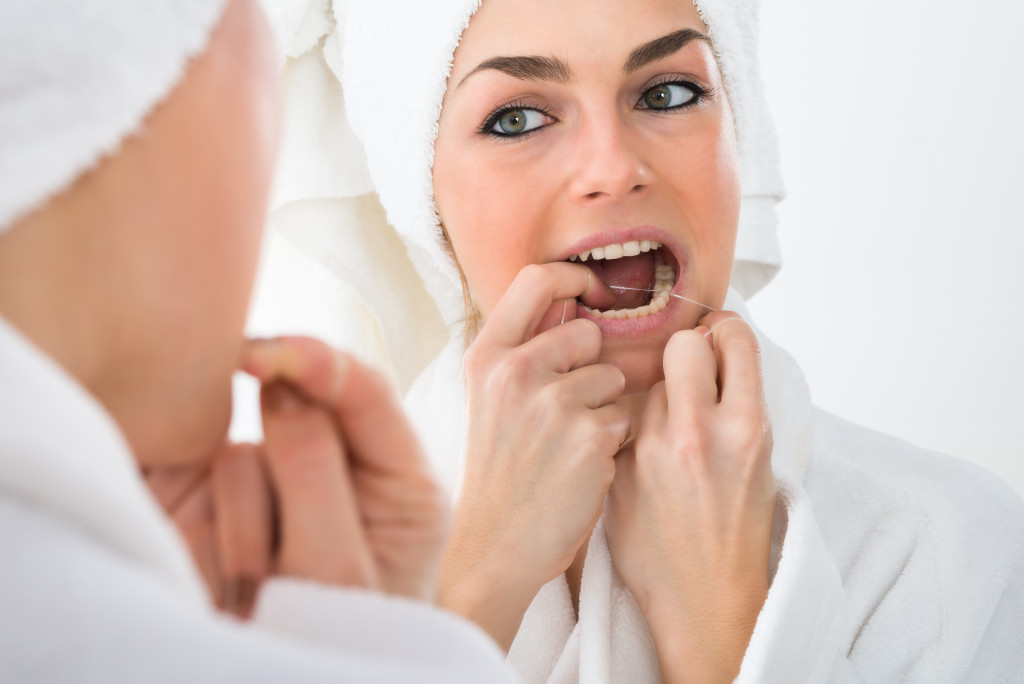 woman flossing after brushing teeth