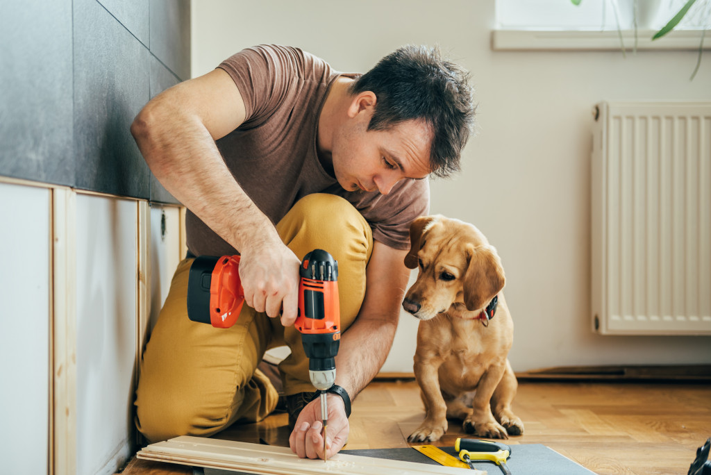 man drilling wood with dog