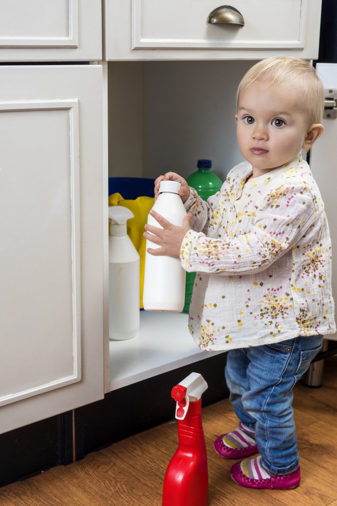 child holding cleaning products