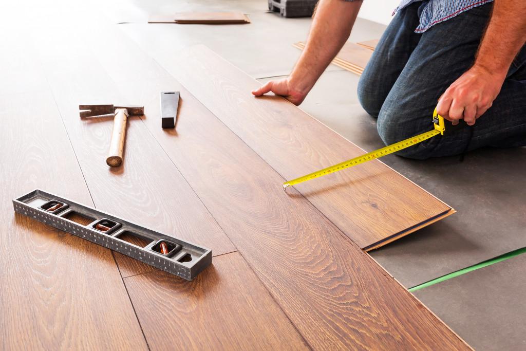 man installing wooden floor boards