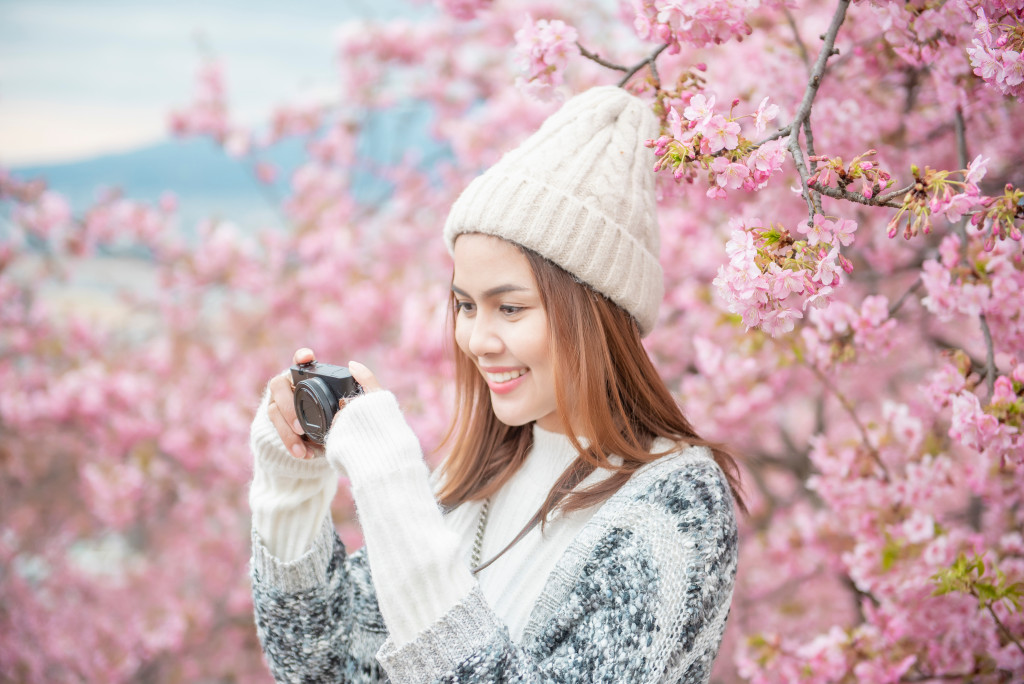 girl holding a camera with cherry blossom trees behind her