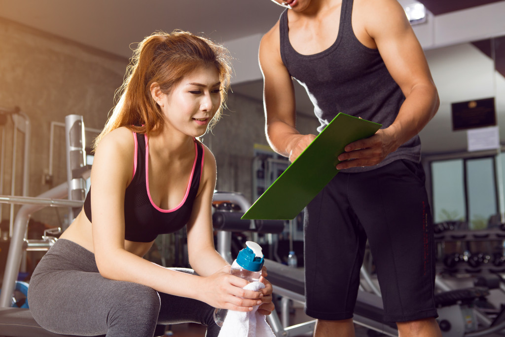 A woman and man talking in the gym